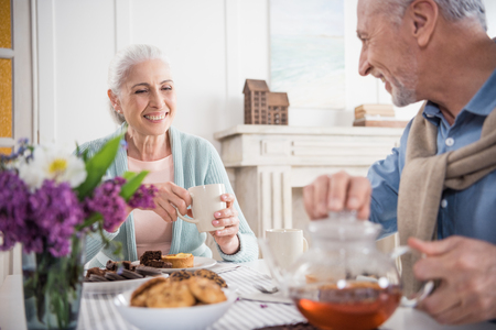 grey haired couple having breakfast at home
