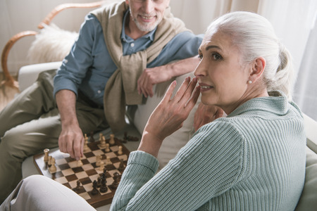 grey haired couple playing chess at home
