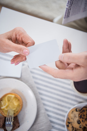 man passing blank card to woman during breakfast