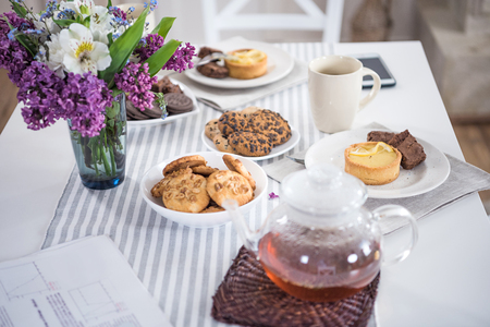 lilac flowers with tea and various pastry with cookies