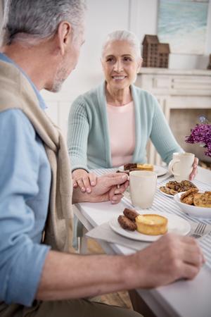 노인 커플 아침 식사하는 동안 손을 잡고 스톡 콘텐츠
