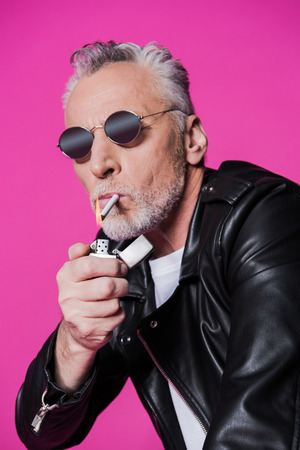 handsome senior man in sunglasses and leather jacket holding lighter and smoking cigarette