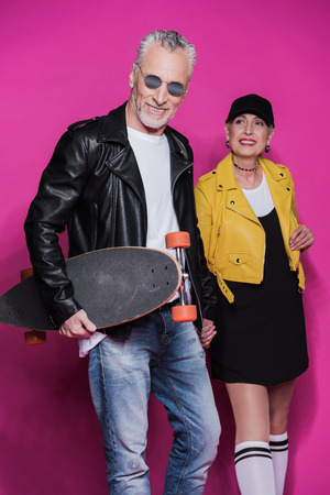 Handsome senior man with skateboard and stylish beautiful woman standing together