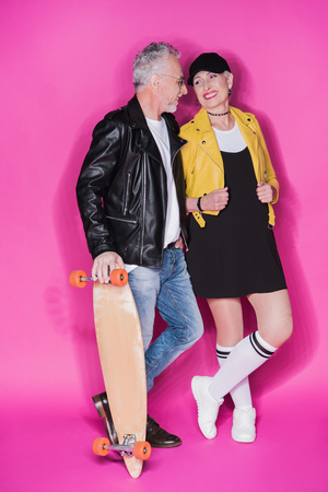 senior man with skateboard and stylish beautiful woman standing together isolated on pink
