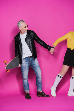 senior couple in leather jackets posing with skateboard and holding hands isolated on pink