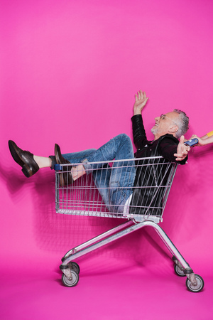 cheerful stylish senior man having fun while sitting in shopping trolley
