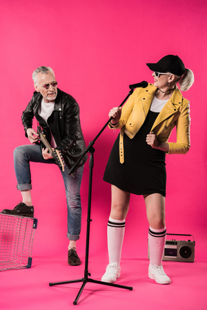 Smiling stylish senior couple performing rock and roll music Stock Photo