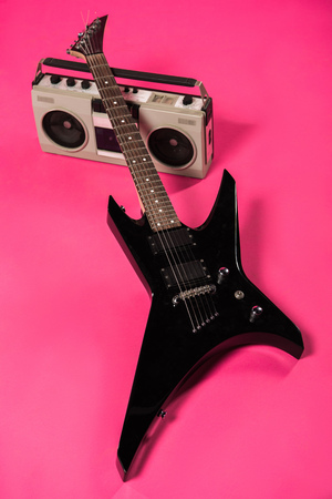 electric guitar and tape recorder isolated on pink Stock Photo