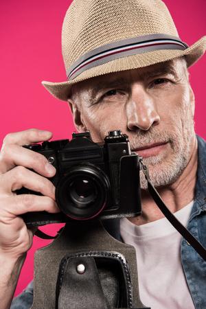 portret van zelfbewuste fotograaf met fotocamera en camera te kijken