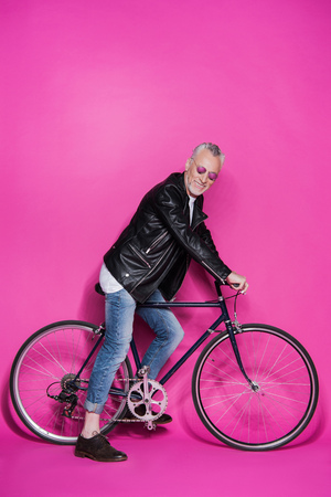 happy fashionable senior man wearing leather jacket, sunglesses and riding bicycle Stock Photo