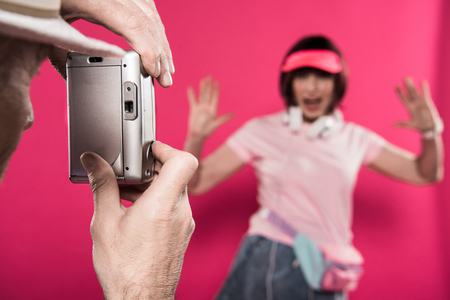 man taking picture of wife isolated on pink