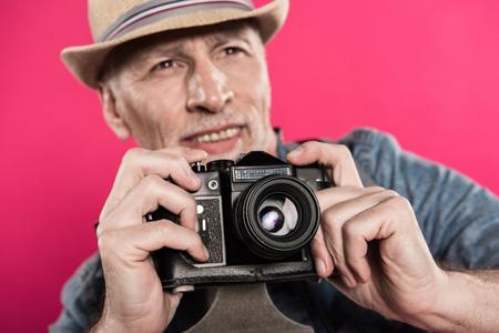 selectieve aandacht van lachende man met retro fotocamera wegkijken Stockfoto