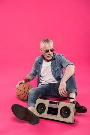 senior man sitting on floor with tape recorder and basketball ball 版權商用圖片