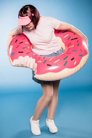woman standing with swimming tube in form of doughnut