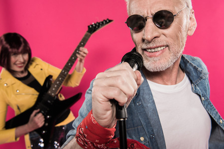 stylish senior couple singing in microphone and playing electric guitar