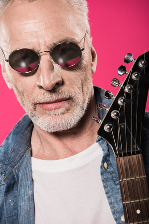 handsome stylish senior man in sunglasses holding electric guitar