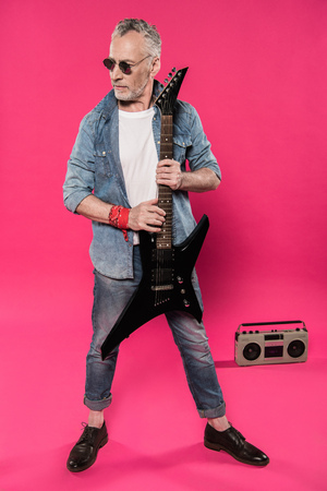 grabadora: senior man in sunglasses and denim jacket holding electric guitar and looking away