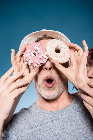 elderly couple fooling around with sweet doughnuts Stock Photo