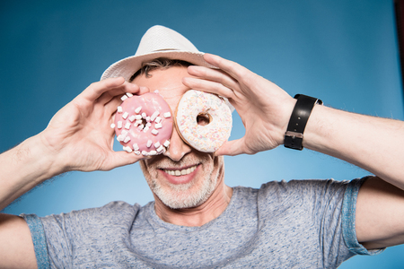 elderly casual man holding donuts in front of eyes Stock fotó