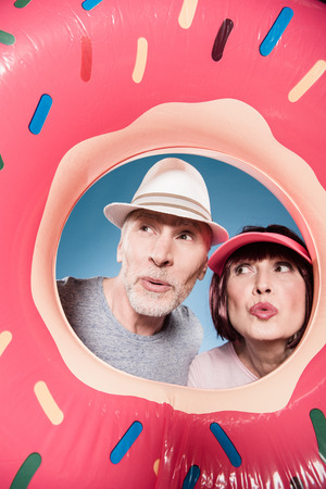 elderly couple with facial expression into swimming tube