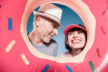 carefree elderly couple smiling into swimming tube