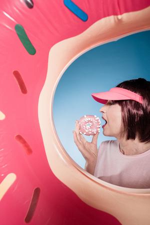 woman eating sweet doughnut into swimming tube