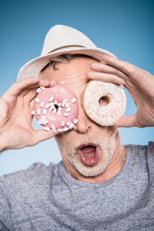 elderly casual man holding donuts in front of eyes Stock Photo