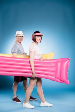 senior couple looking at camera and holding swimming mattresses during walk