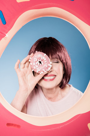 woman holding doughnut in front of eye into swimming tube Stock Photo