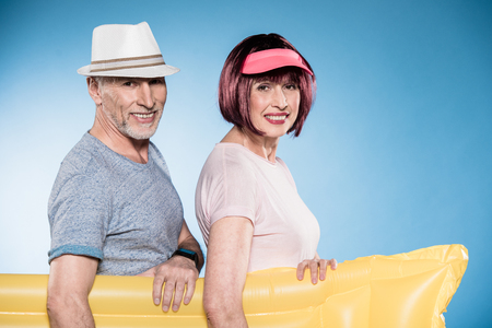 elderly couple looking at camera and holding swimming mattress