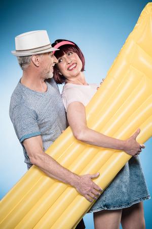 casual elderly couple holding swimming mattress