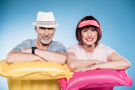 senior couple looking at camera and leaning on colorful swimming mattresses