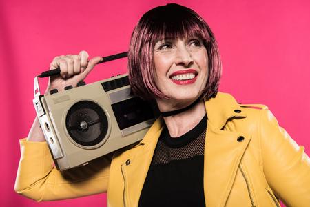 stylish senior woman holding tape recorder isolated on pink