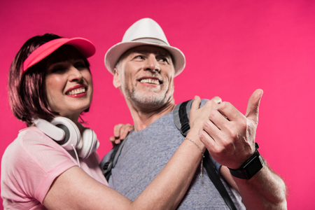 low angle view of smiling couple in stylish clothing looking away