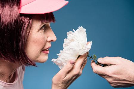 elderly woman holding and smelling white flower Stock fotó - 82920826