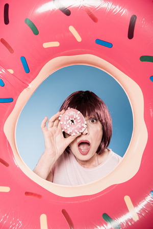 woman with facial expression holding doughnut in front of eye into swimming tube Stock Photo