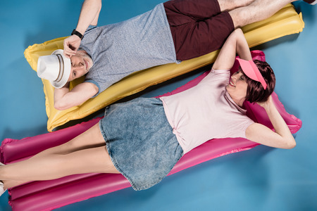 elderly couple lying on colorful swimming mattresses