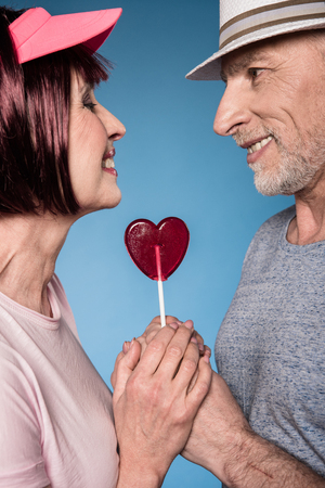 stylish elderly couple holding hands with lollipop in form of heart