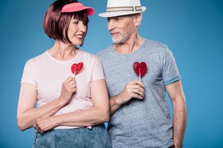 fashionable elderly couple smiling and holding lollipops Stock Photo
