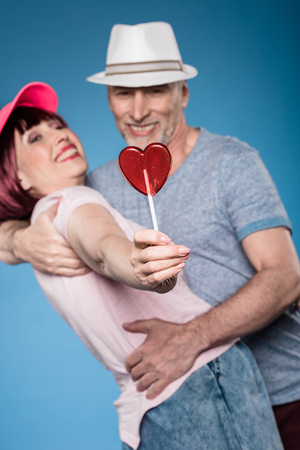 elderly couple hugging and holding lollipop in form of heart