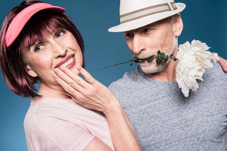 stylish elderly couple embracing and posing with white flower Stock Photo