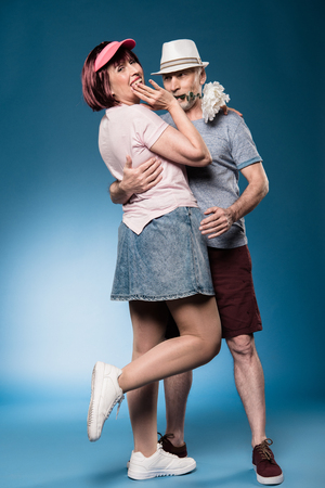 fashionable elderly couple embracing and posing with white flower