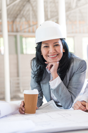 asian contractor in formal wear holding coffee cup and looking at camera