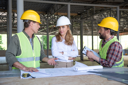builders and contractor talking during work on construction site Фото со стока