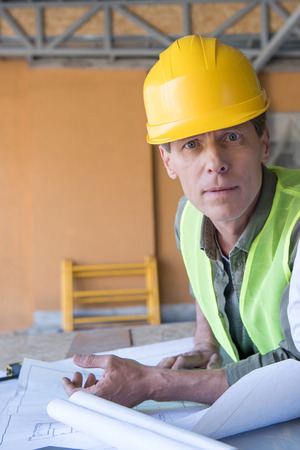 architect looking at camera while working with blueprints at construction site Stock Photo