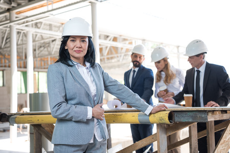 aged asian contractor looking at camera during meeting at construction site Stock Photo