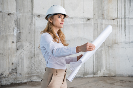 blonde architect in helmet working with blueprint and looking away at construction site