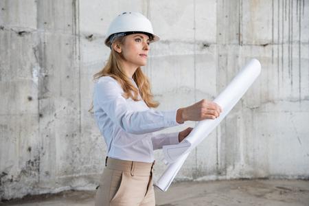 Arquiteto loiro no capacete trabalhando com blueprint e olhando para longe no canteiro de obras Foto de archivo - 82925515