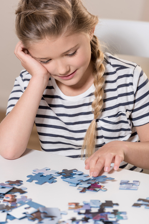 Girl playing puzzle on table Stock fotó