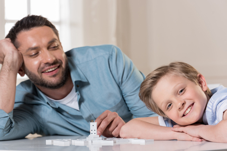 Father and son at table with domino pieces
